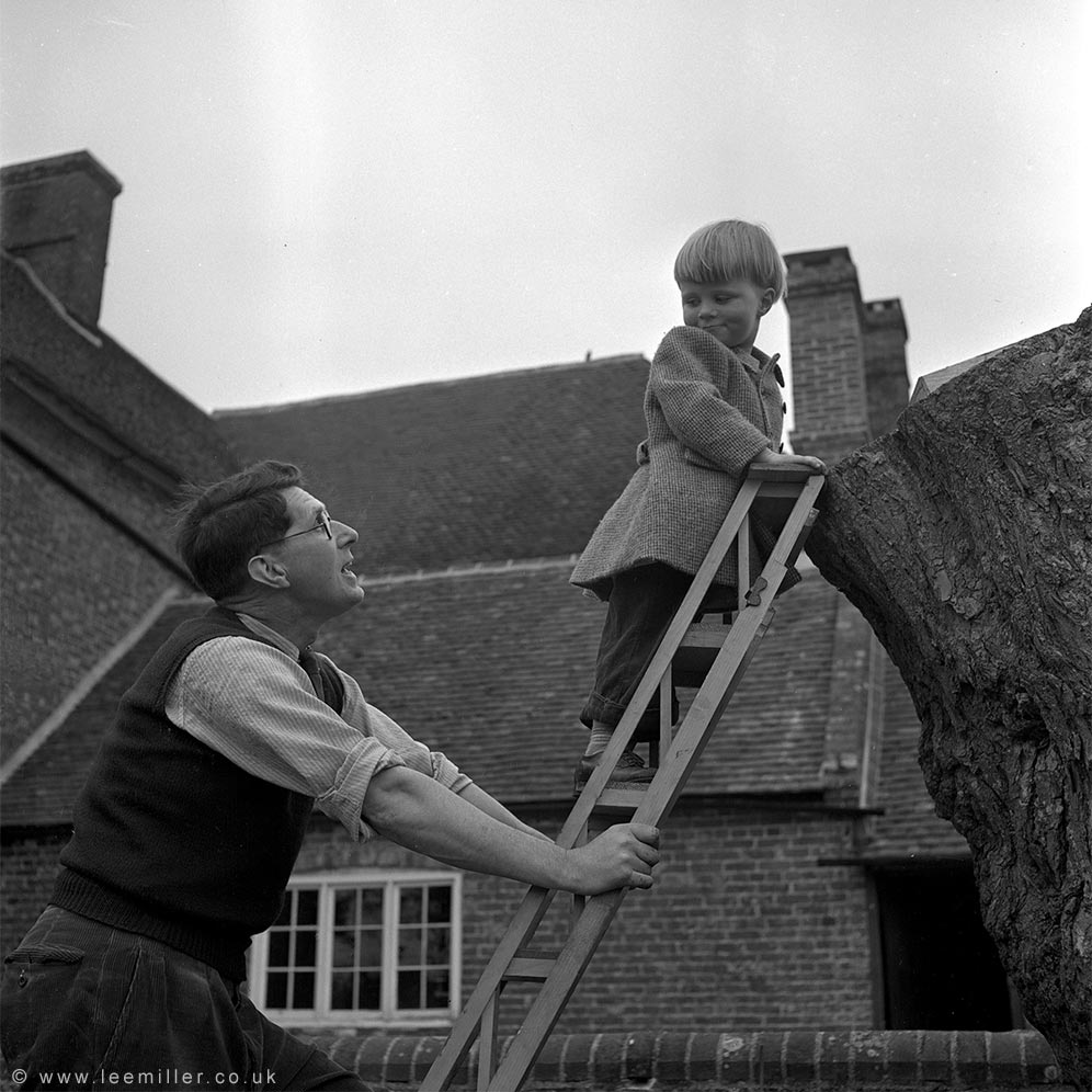 Roland Penrose holding ladder with young Antony Penrose climbing in the garden at Farleys in 1950