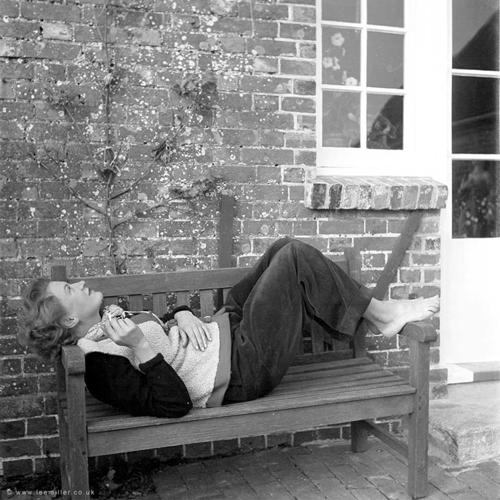 Lee Miller reclining on a bench outside Farleys House