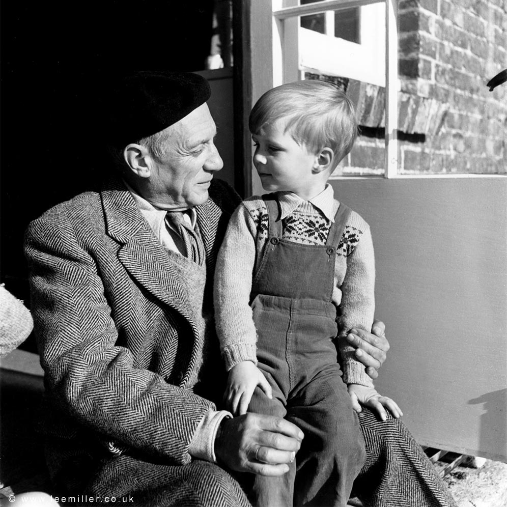 Antony Penrose aged 4 sitting on Picasso's knee in on the steps outside the sitting room door at Farleys
