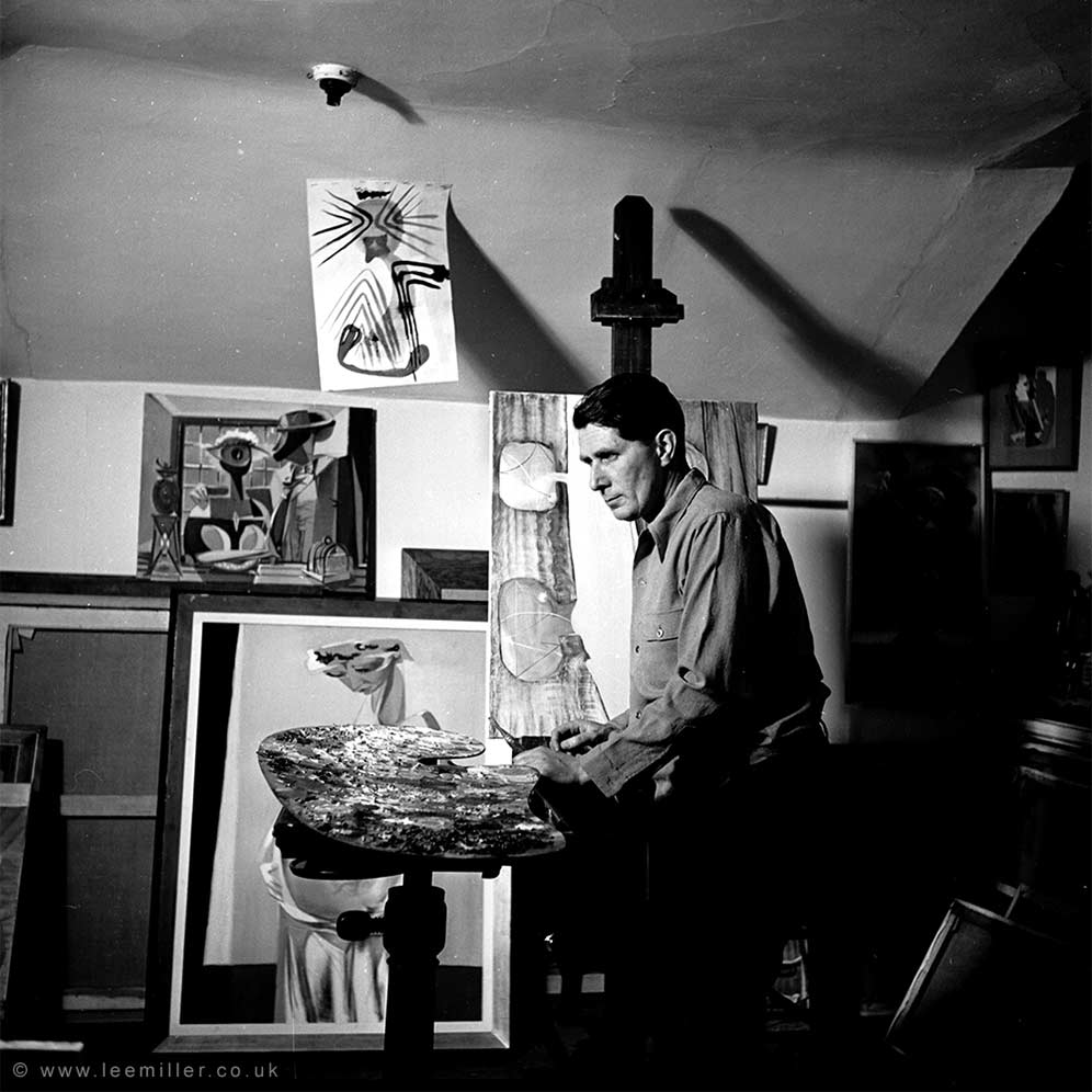 Roland Penrose in his studio surrounded by his paintings