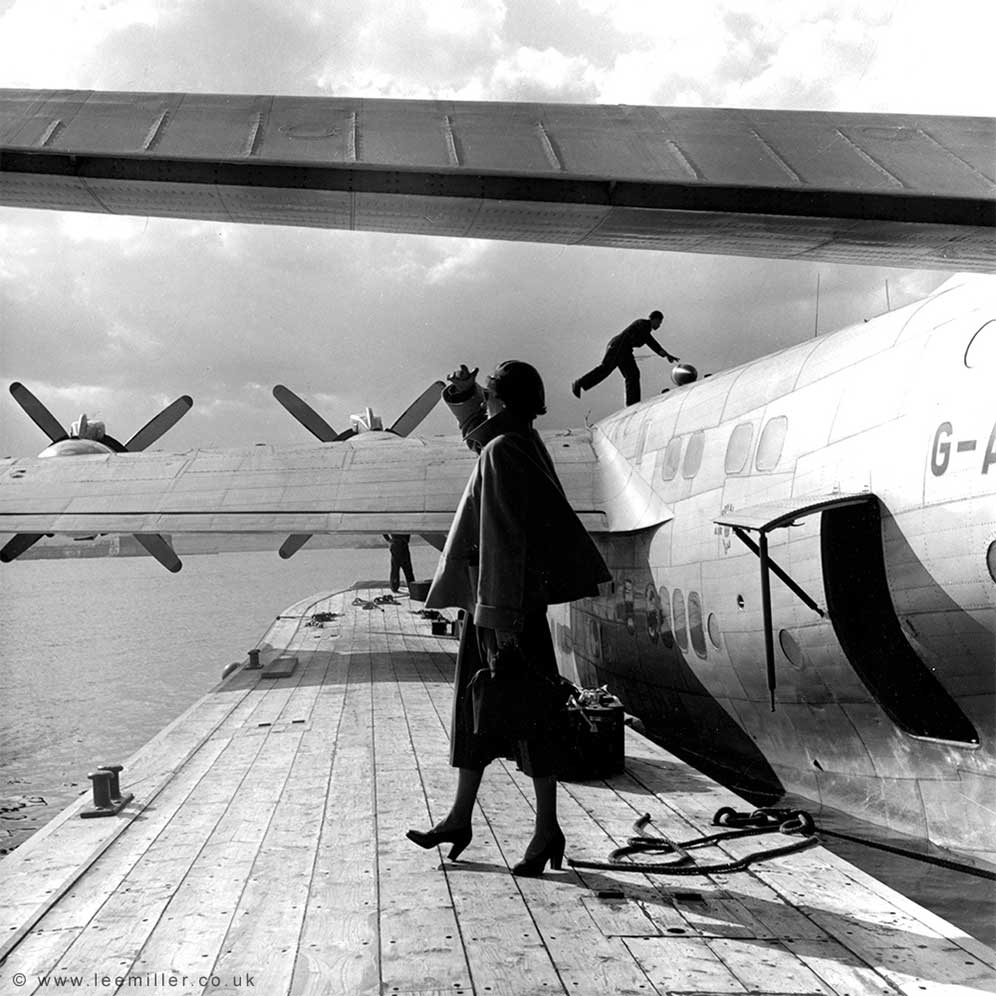 Fashion model standing next to flying boat in Augusta Harbour, Sicily