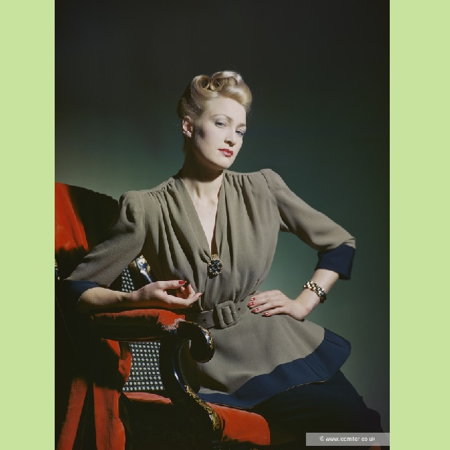 Colour image of model wearing a green tapered wool blouse tapered at the waist with a belt